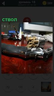 На поверхности стола лежит ствол револьвера и барабан с патронами
