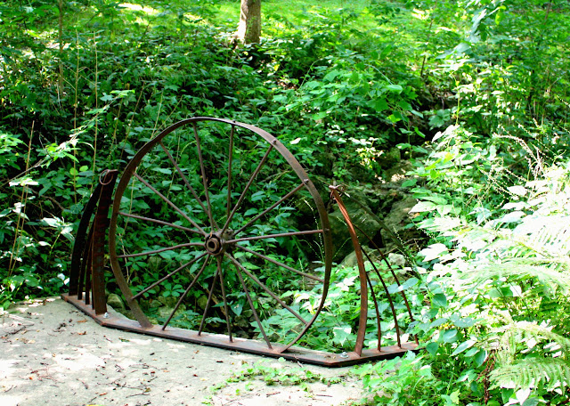 Whimsical wheel sculpture with a forest background made by a local artist in Galena, IL.