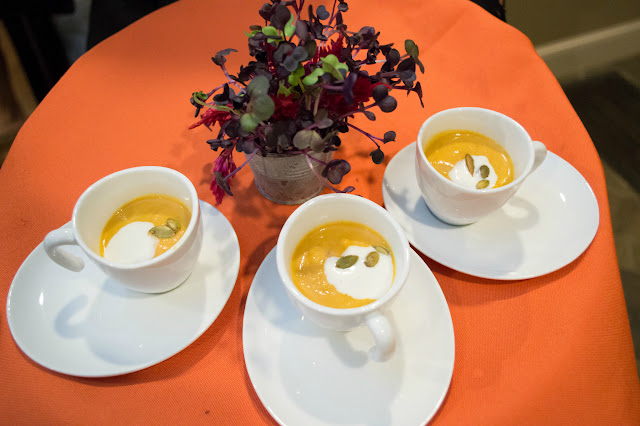 Pumpkin bisque shooters with maple creme fraiche and spiced pepitas