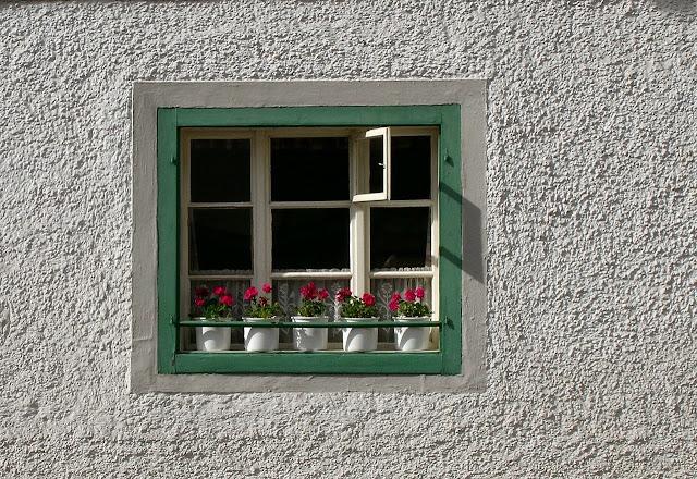 Janela com duas bordas, a primeira pintada de branca e a segunda de verde, há também vasos de flores decorando a faixada, está em uma parede branca.