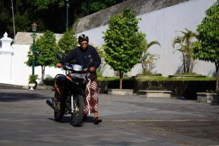 Abdi Dalem mendorong sepeda motor di dalam kompleks kraton