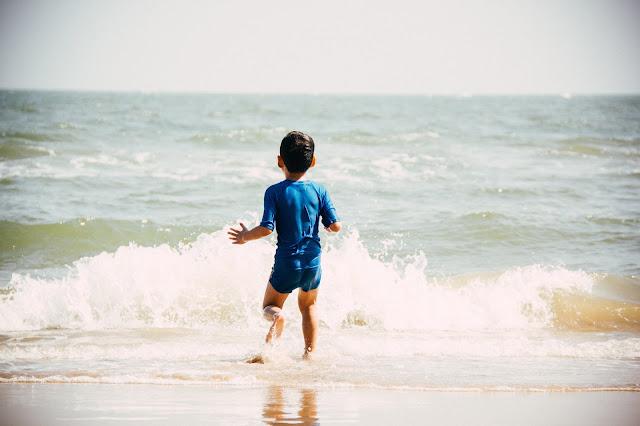 Niño corriendo para entrar en el mar