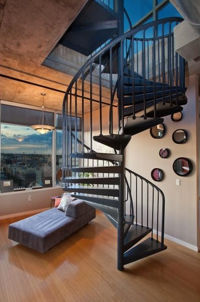 Round staircase to the roof terrace and a single sofa in Denver penthouse apartment