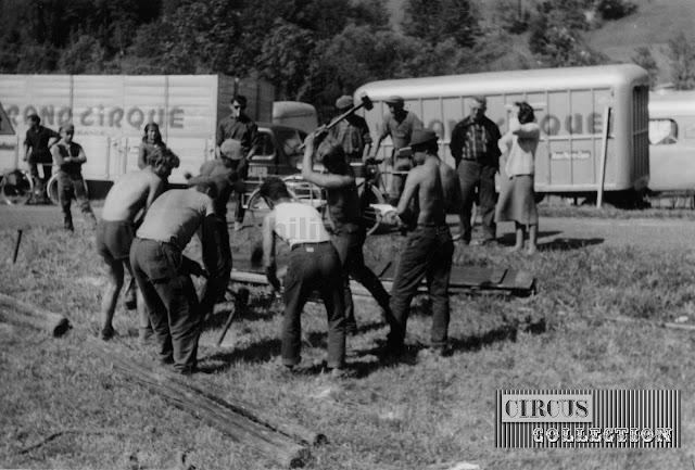 les ouvriers du cirque enfoncent a l'aide de grosse masses des pieux en fer pour amarrer le chapiteau