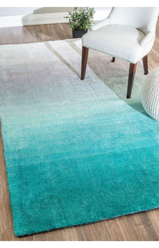 Tapete com padrão ombré em tons de azul, cadeira tipo poltrona em branco e pufe branco com capa de crochet