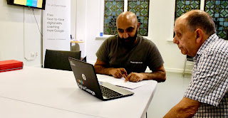A man in a blue tshirt with Google in rainbow font sat on a bright white oval table with a man in a blue shirt with a dark rectangular laptop on a bright background.