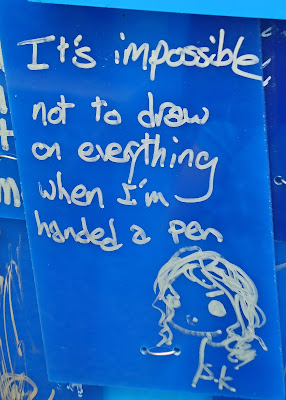 "Graffiti--""It's impossible not to draw on everything when I'm handed a pen"" and a drawing of a girl. Silver ink on royal blue background."
