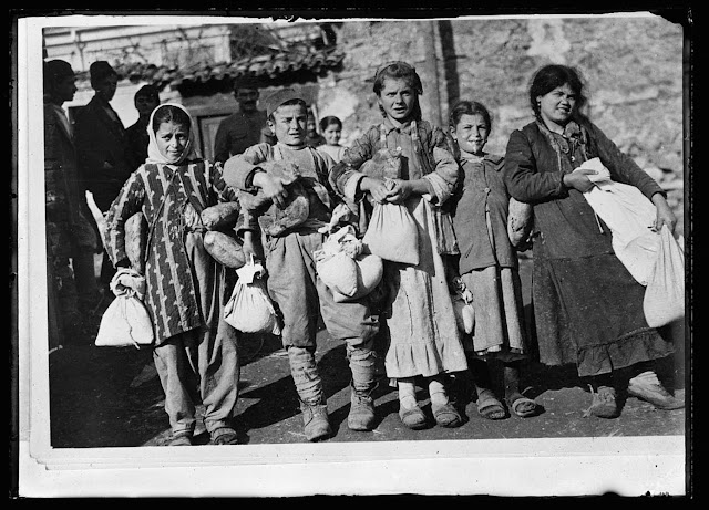 Children of Monastir calling at the depot of the A.R.C. set up in an old shelled building for their rations of bread, lard and other foodstuffs sent from the United States to check the starvation in Southern Serbia. Each of the inhabitants is given a two pound loaf of bread, a pound of rice, beans and sugar each week