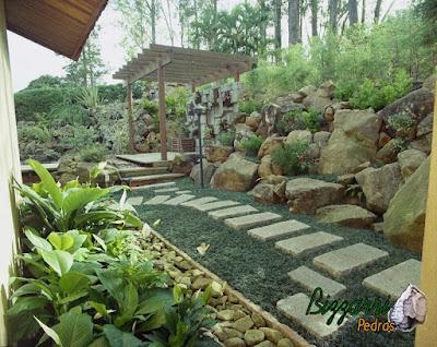 Caminhos de pedra folheta com junta de grama preta na execução do paisagismo.