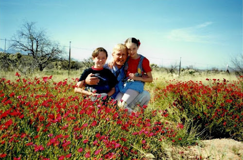 A blonde man with a brunette boy (in a blue shirt) and girl (in a a red shirt)sitting in a field of red flowers.