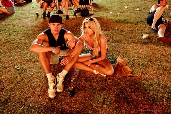 A couple chill out on the grass, night above the dance area. Harbour Life Music Festival Sydney 2016. Photographed by Kent Johnson for Street Fashion Sydney.