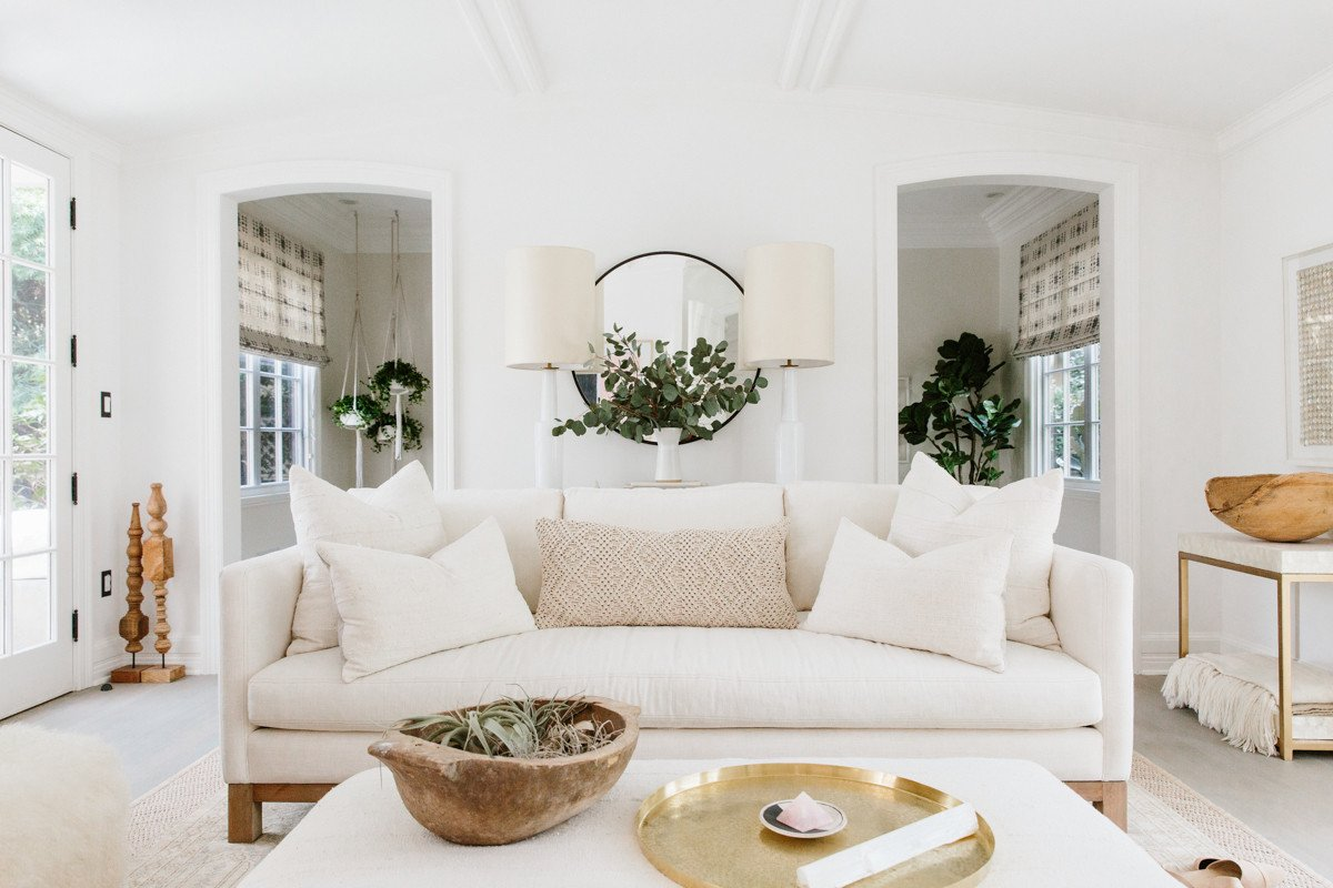 Erin Fetherston Living Room With White Sofa, Brass Tray, Rustic Wood Bowl,  ...