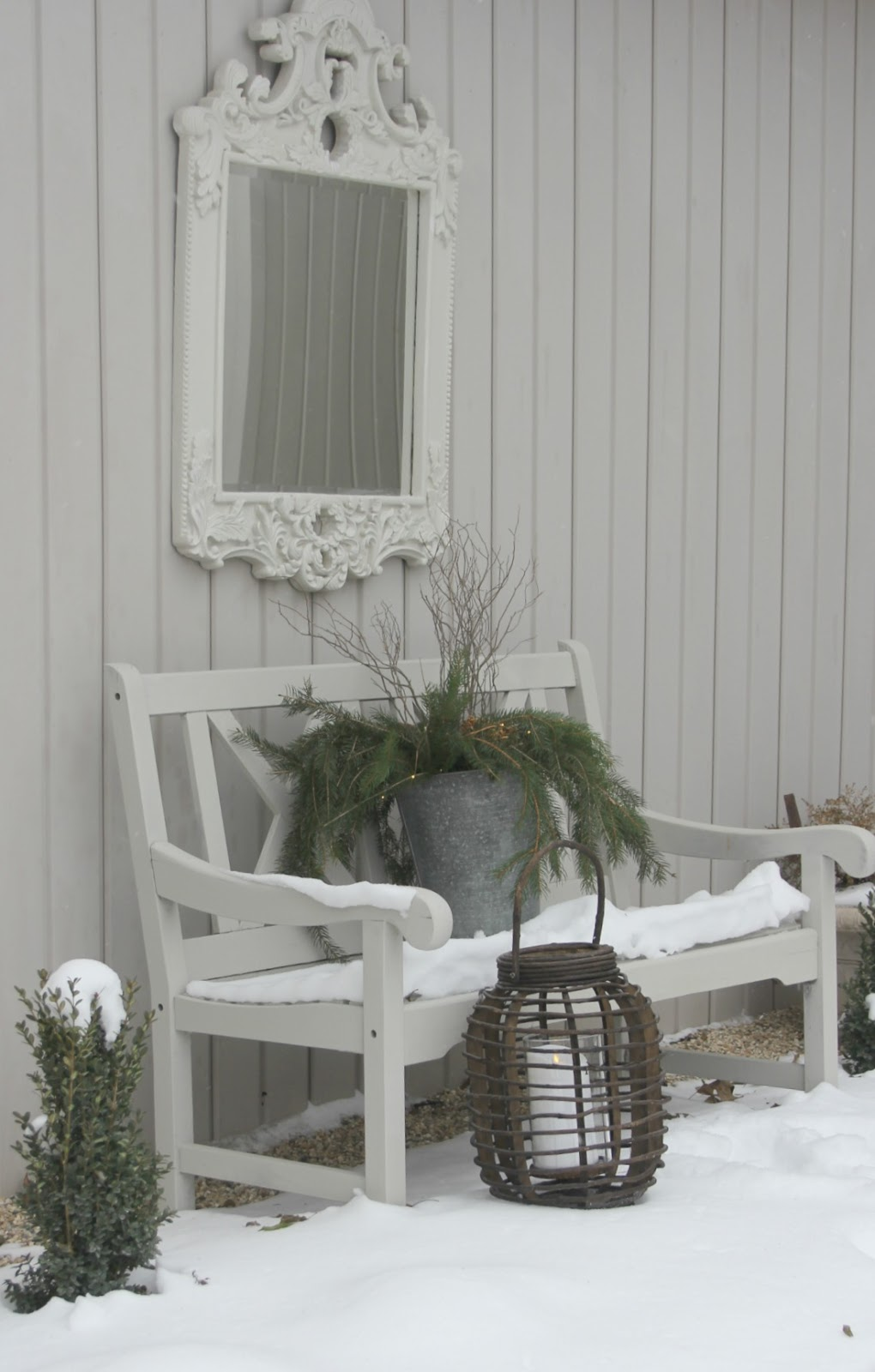 Snow covered bench with bucket of Christmas greenery, wood lantern, and French mirror - Hello Lovely Studio