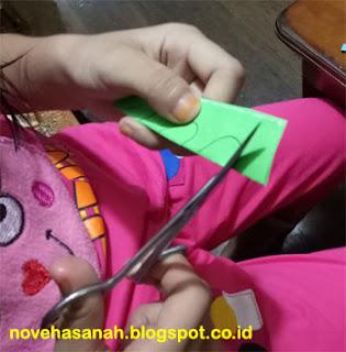 menggunting ornamen berbentuk hati untuk membuat kerajinan tangan anak SD