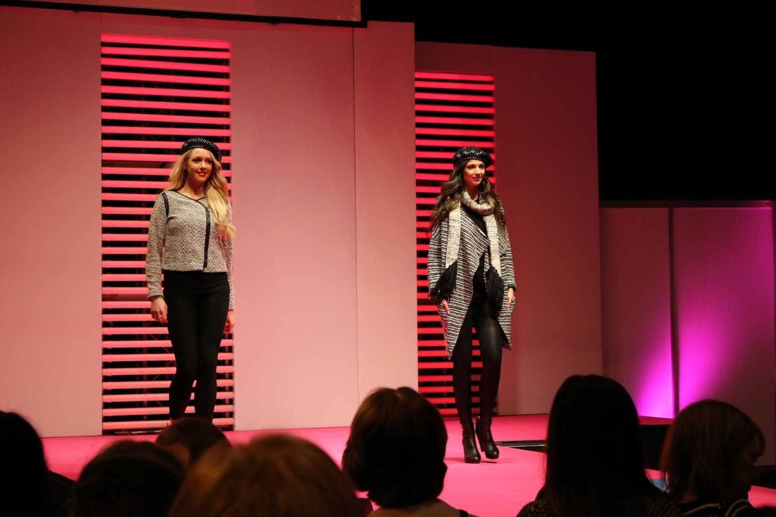 a photo of the fashion cat walk at girls day out show 2015. there are two models walking on the run way wearing winter clothes