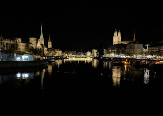 Nighttime view of the towers of the Grossmünster church and other church towers reflected in the lake, Zürich, Switzerland