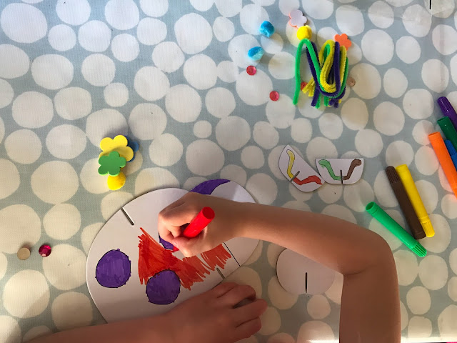 A cardboard ladybird being coloured in red and purple