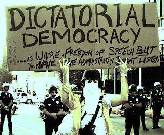 Man holds a sign proclaiming 'Dictatorial Democracy' with police in Background