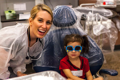 Image of dental hygiene students and child in dental chair with sunglasses