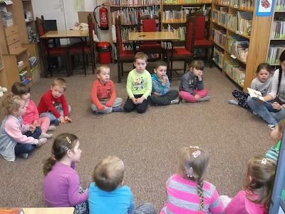 Dzieci siedzą w kole i słuchają książeczki