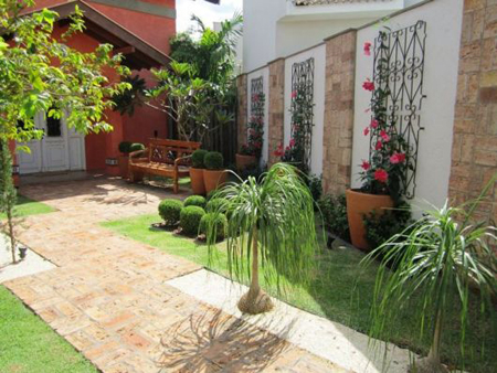 jardim amplo com banco rústico, área gramada e floreiras nas paredes