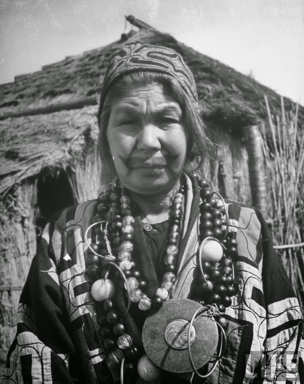 Wife of Ainu village chief wearing traditional necklaces, 1946