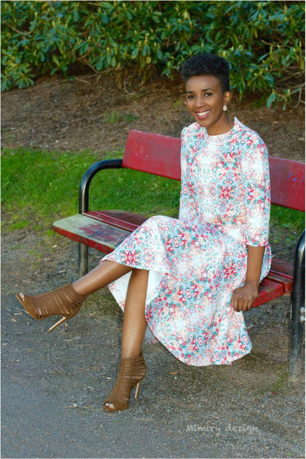smiling woman in a flowerly outfit and a pair of Zara Heels