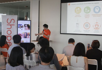 Source: Shopee. Feng shows off the Shopee e-commerce platform on a screen replicating what is on his phone.