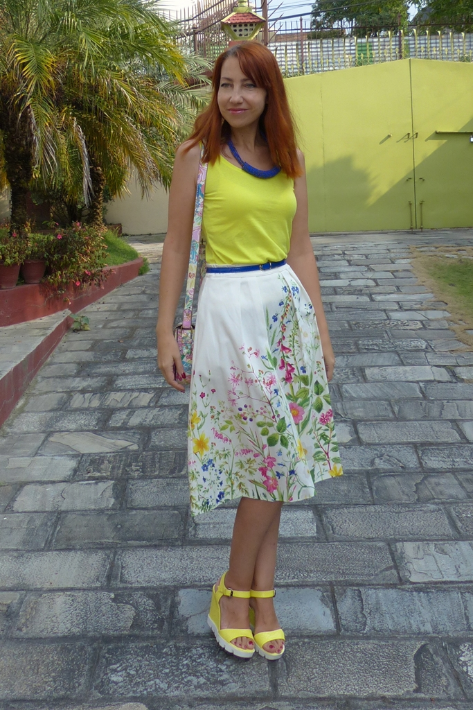 Floral print skirt with yellow top and blue accessories