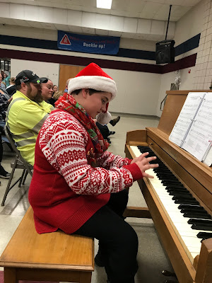 A kid wearing Christmas clothes and a santa hat is sitting on a bench playing a piano
