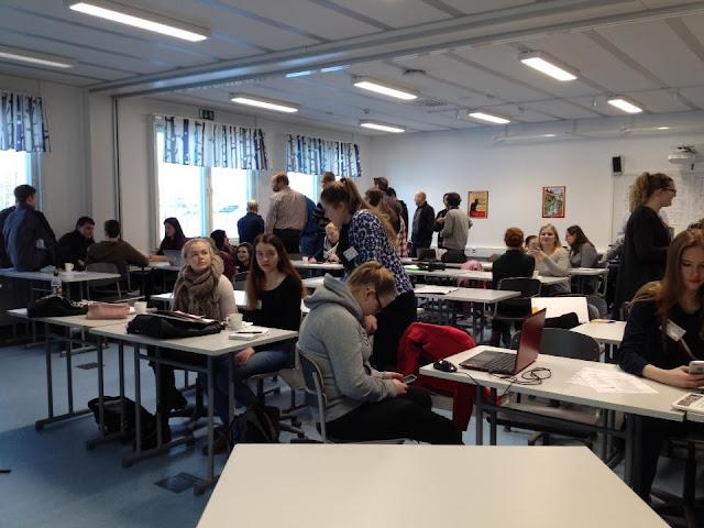 Koululaisia istuu ja seisoo pulpettien keskellä luokkahuoneessa