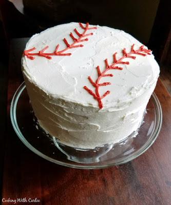 tall round cake decorated like a baseball
