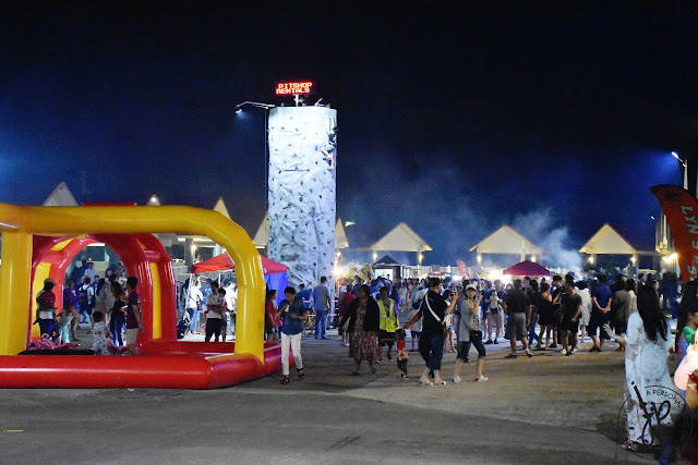 people walking at night market, inflatable play area, wall climbing
