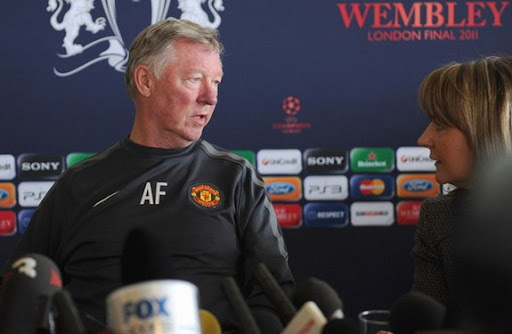 Sir Alex Ferguson speaks to his press officer during a press conference