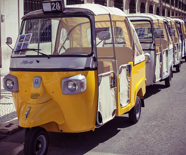 A line of tuk tuks parked along a street in Lisbon
