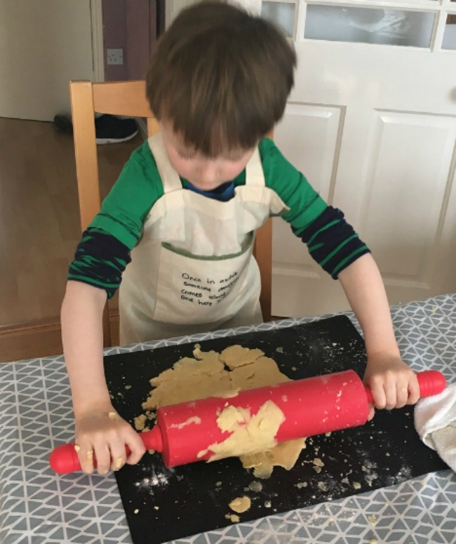 boy-rolling-cookie-dough-with-big-red-rolling-pin