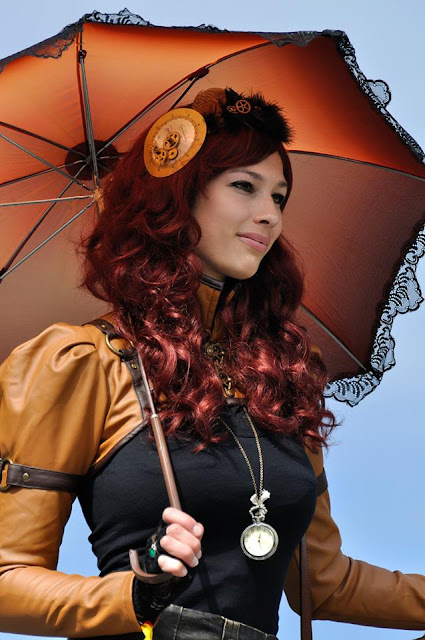 Woman wearing Steampunk clothing in shades of orange/rust color. Bolero jacket, fascinator, pocketwatch, gloves, parasol/umbrella on redhead