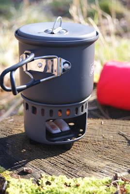 Der Kocher steht zusammengebaut auf einem Baumstumpf. Im Kocher brennen unten zwei Brennstofftabletten. Der Griff des Topfes ist ausgeklappt und der Deckel ist aufgelegt