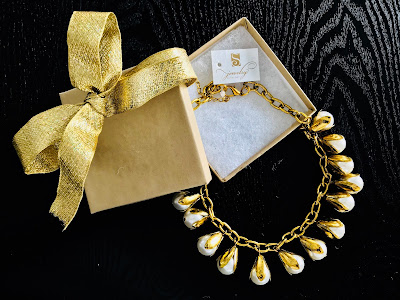 Photo of pearl necklace in a box with a gold bow