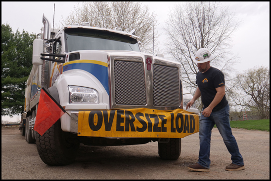 Derwin Whitmer, owner of Dig-It Excavating, stands with one of his  Kenworth T880s