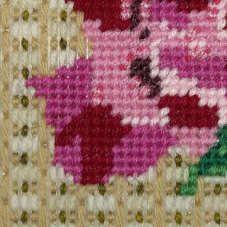 Detail of needlepoint rose and background