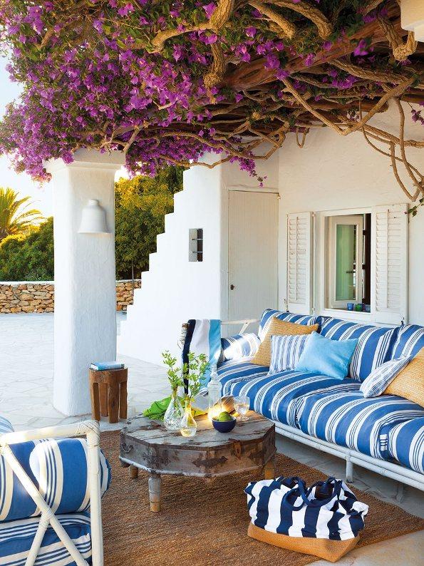 terraza con muebles de mimbre y cojines azules