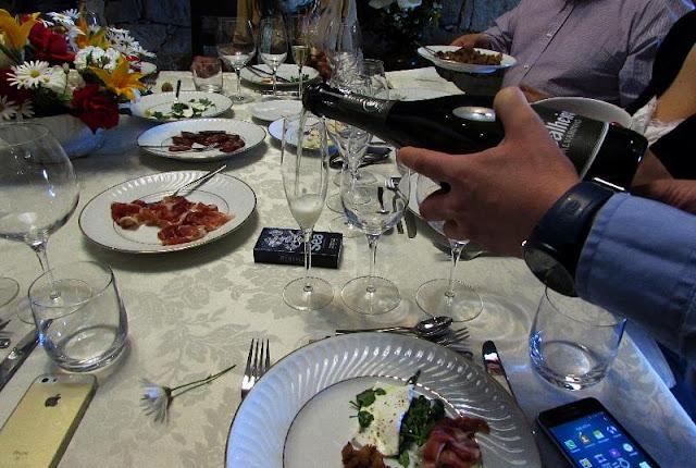 servindo vinho em mesa de almoço com produtos regionais