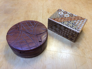 A fish-shaped puzzle box and an elaborately inlaid Japanese puzzle box
