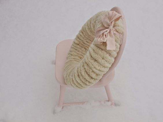 Woolly white handmade pom pom wreath with pink ribbon on pink chair in snow