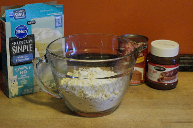 A mixing bowl, on the counter, with the powdered cake mix in it.