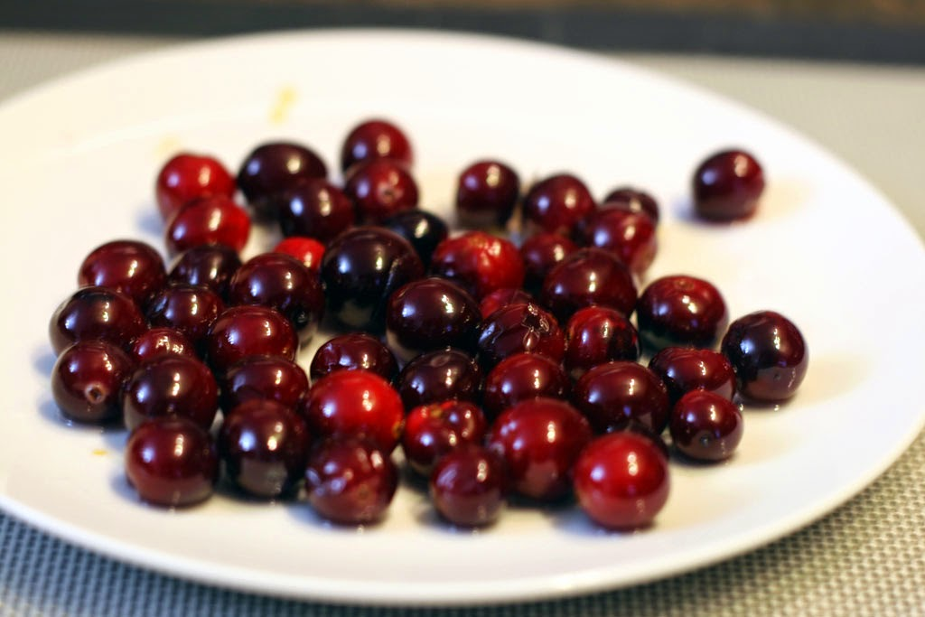 A plate of red cranberries coated in simple syrup.