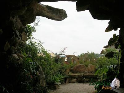 Detalhe da construção da gruta de pedra, com pedra moledo, de dentro para fora, com o banco de pedra, o piso de pedrisco e a execução do paisagismo.