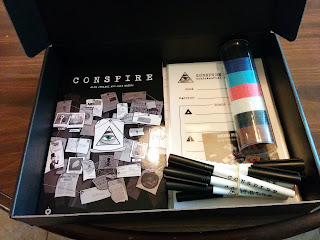 The Conspire Deluxe Set. A flat black box, propped open to reveal the Conspire rulebook, with artwork depicting a typical conspiracy theorist's bulletin board, showing the conspire logo, an eye in a triangle, in the centre. Also in the box is a tube containing poker chips in several different colours, a bundle of dry-erase markers, laminated role sheets, and a Cherry Picked Games business card.
