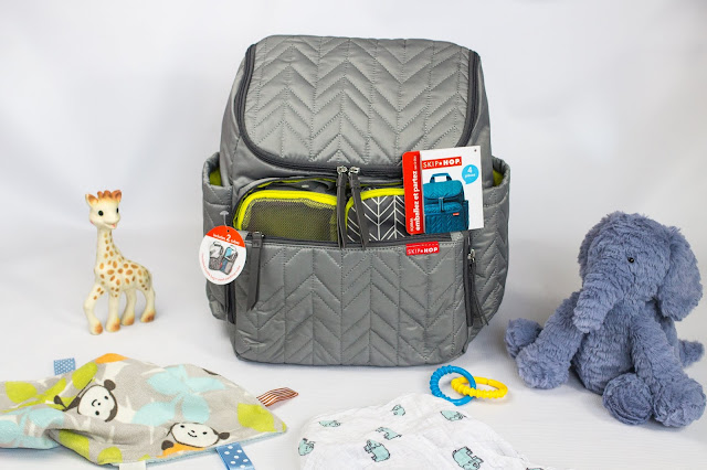 The skip hop forma backpack surrounded by baby items